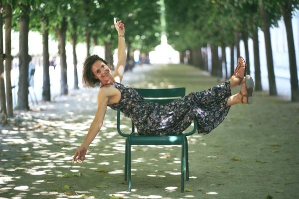 photo de la creatrice assise de travers sur une chaise jambes et bras en l'air dans une allée de parc