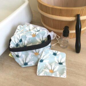 kit carrés démaquillant lavables imprimé grosses fleurs blanches sur fond bleu pale avec pochon de lavage et panière de rangement